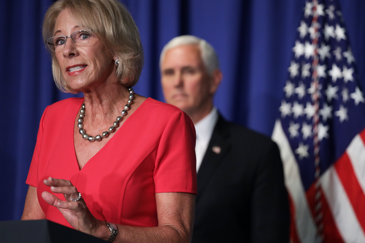 Betsy DeVos speaks as Vice President Mike Pence listens during a press briefing