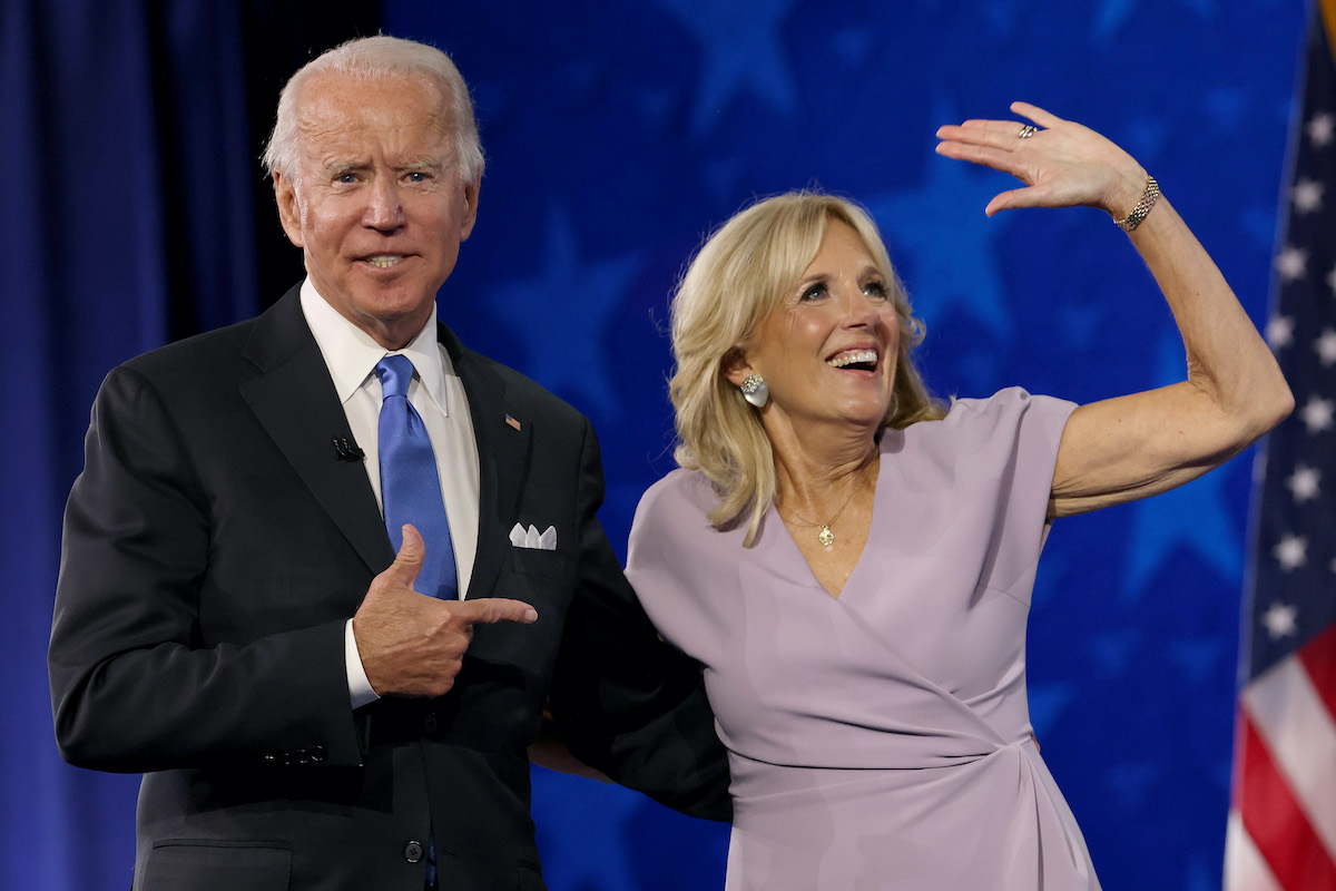 Joe Biden points to his wife Dr Jill Biden as she waves from a stage.