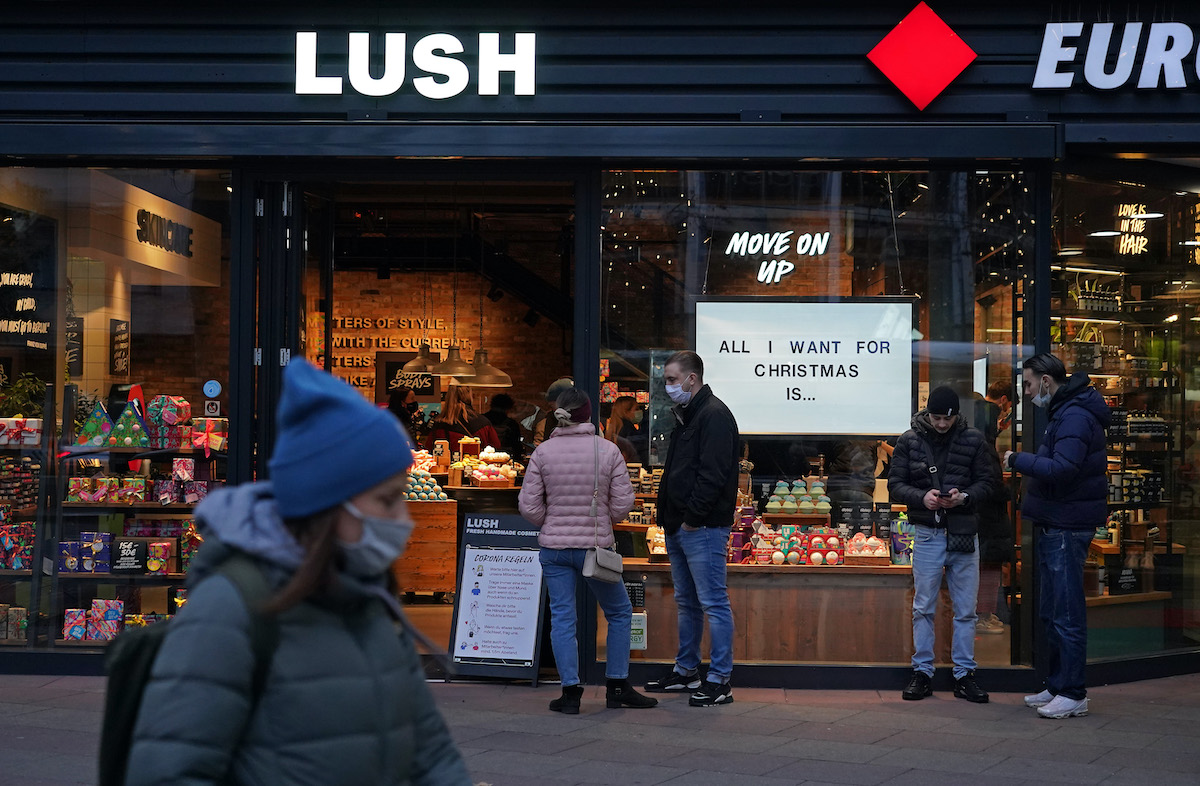 Shoppers wait to enter a Lush cosmetics store with a Christmas theme on Black Friday weekend