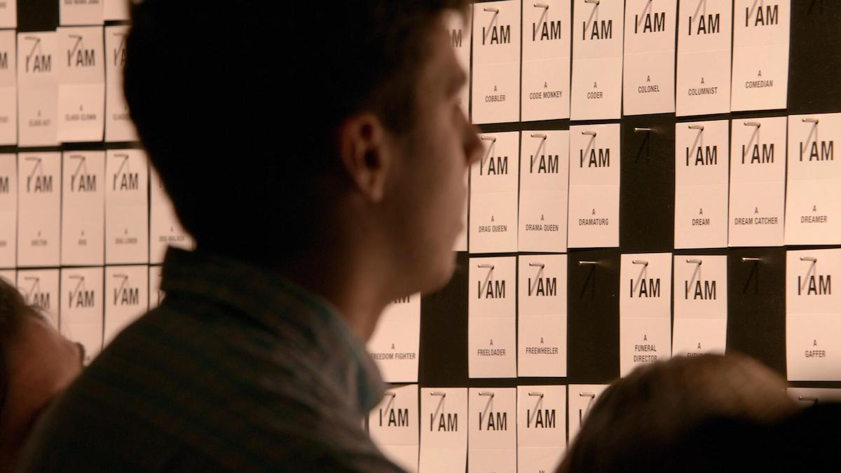 "An audience member looks at a wall of cards reading ""I AM"" with different descriptors on each."