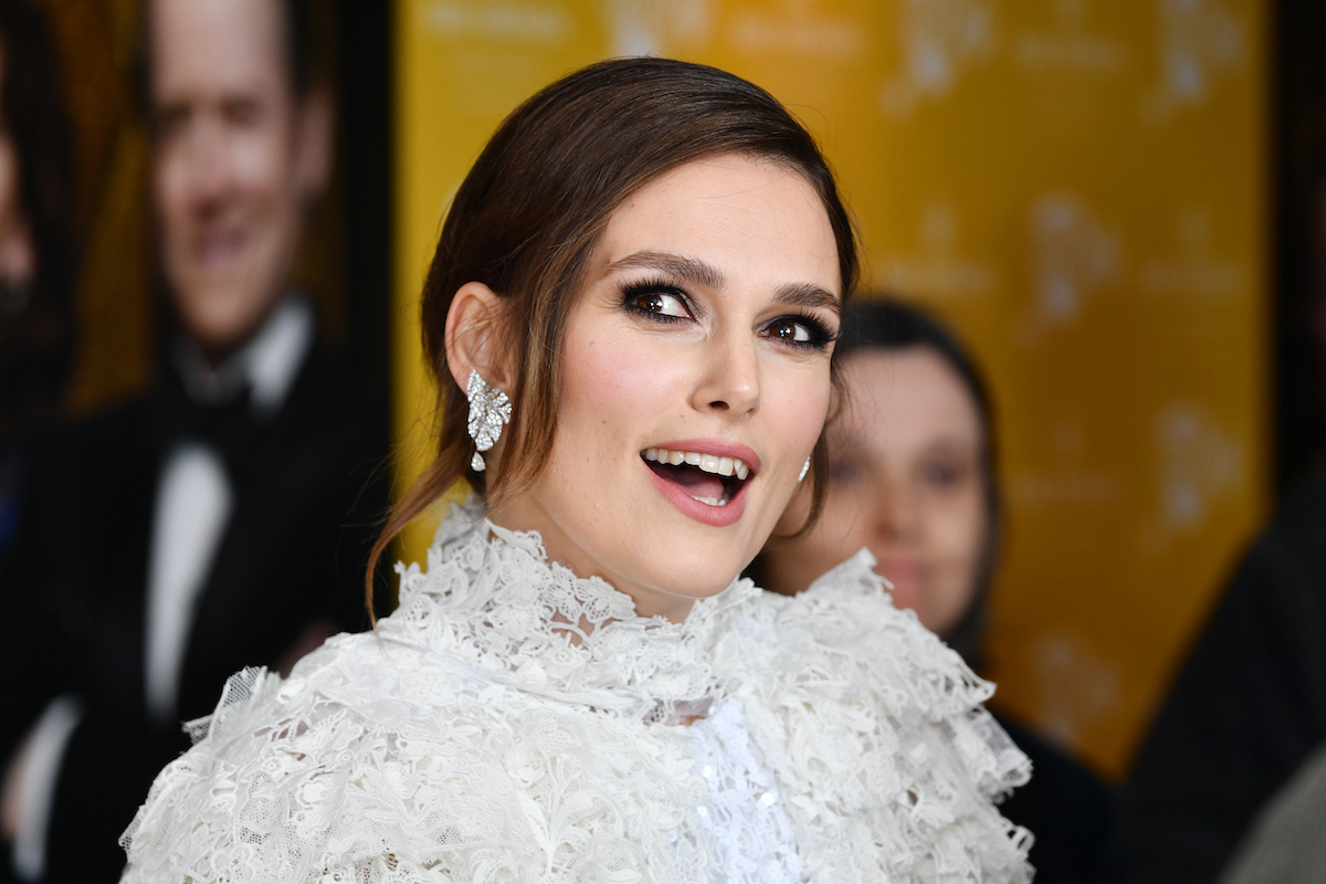 Keira Knightley wears an elaborate white dress on a red carpet.