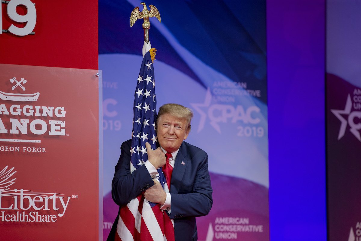 Donald Trump proves how much he loves America by hugging a flag and smirking