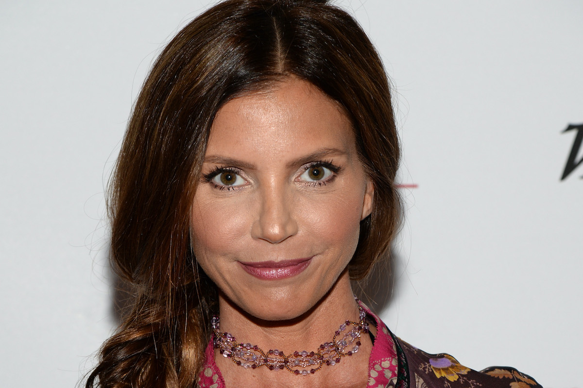 Charisma Carpenter looks at the camera while walking a red carpet for an event.