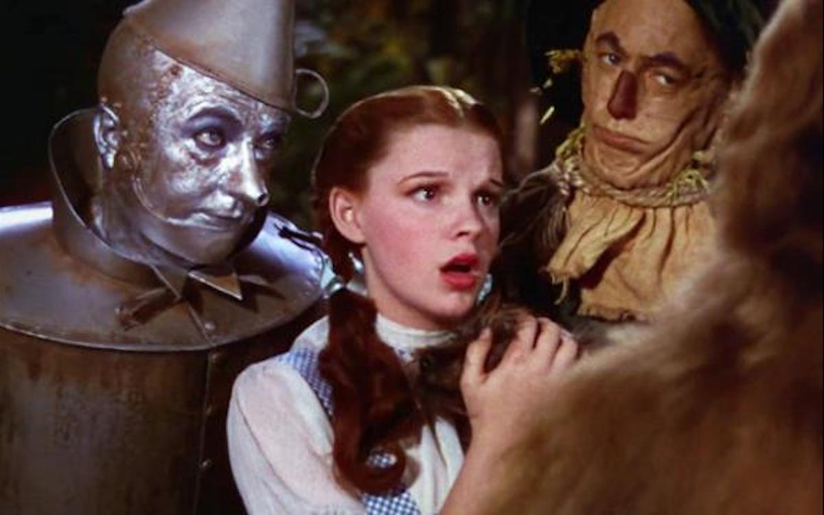 Dorothy, the Tin Man, and the Scarecrow look scared/disapproving in a still from The Wizard of Oz