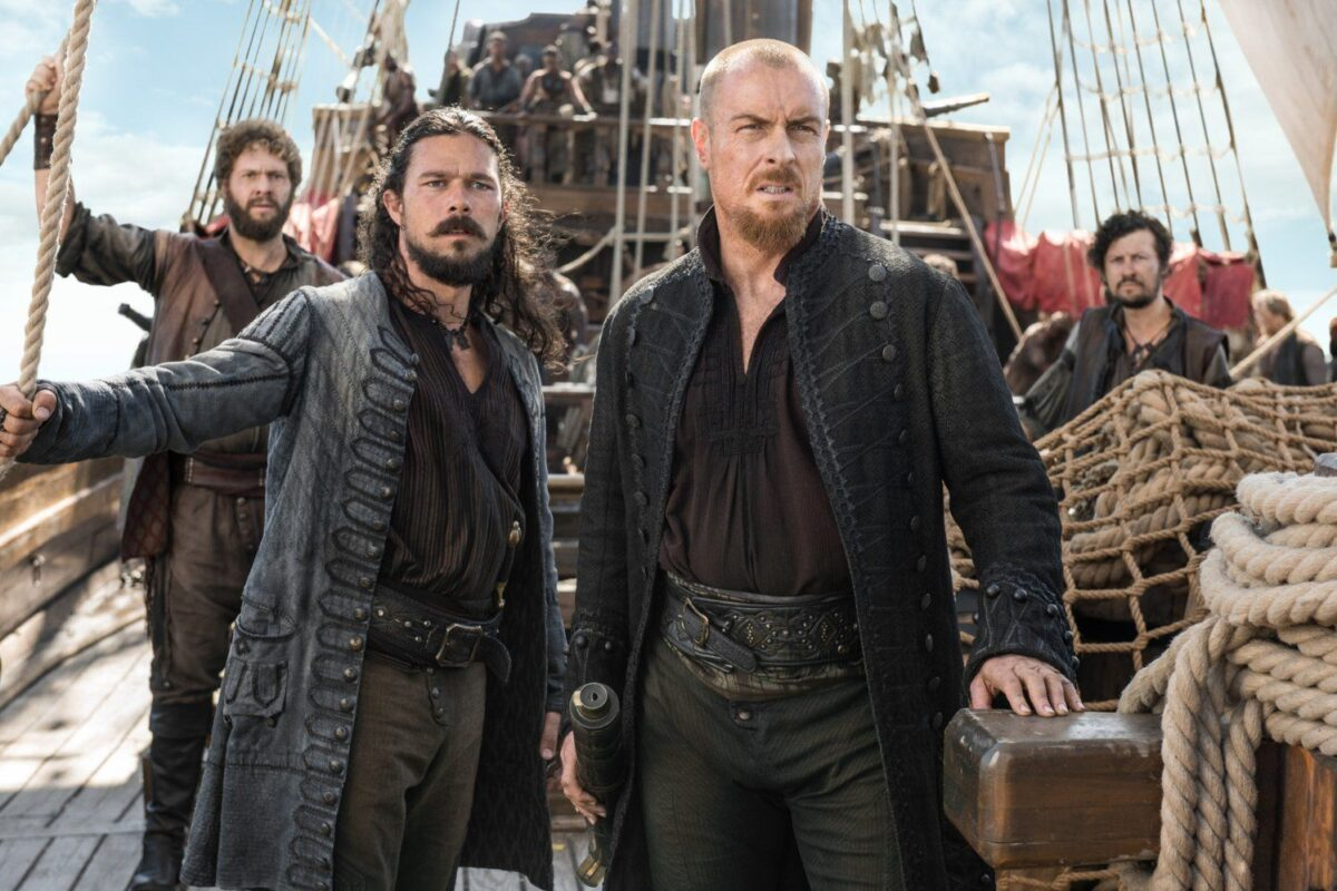 flint and silver look worried and dirty on the deck of a ship in black sails