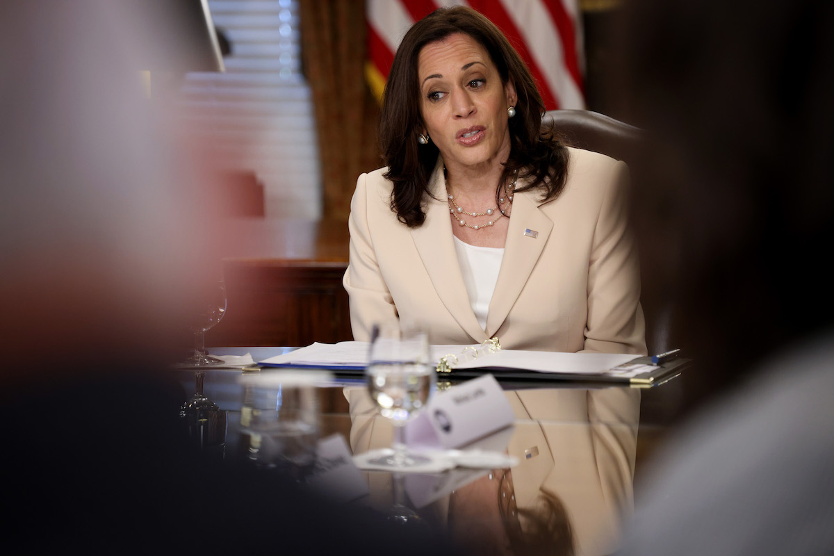 Kamala Harris speaks from a table, viewed through the shoulders of the people sitting across form her.