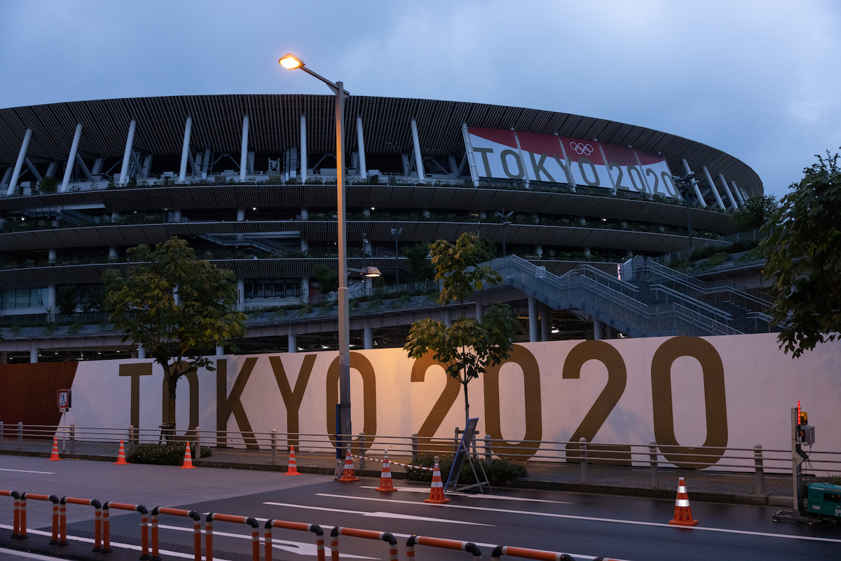 Branding reading TOKYO 2020 is displayed on a fence surrounding the Olympic Stadium