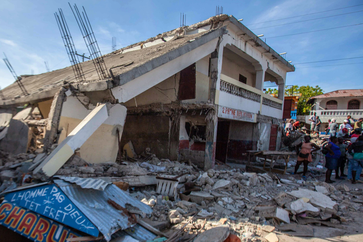 People stand by the debris of a collapsed building after a 7.2-magnitude earthquake struck Haiti on August 16, 2021