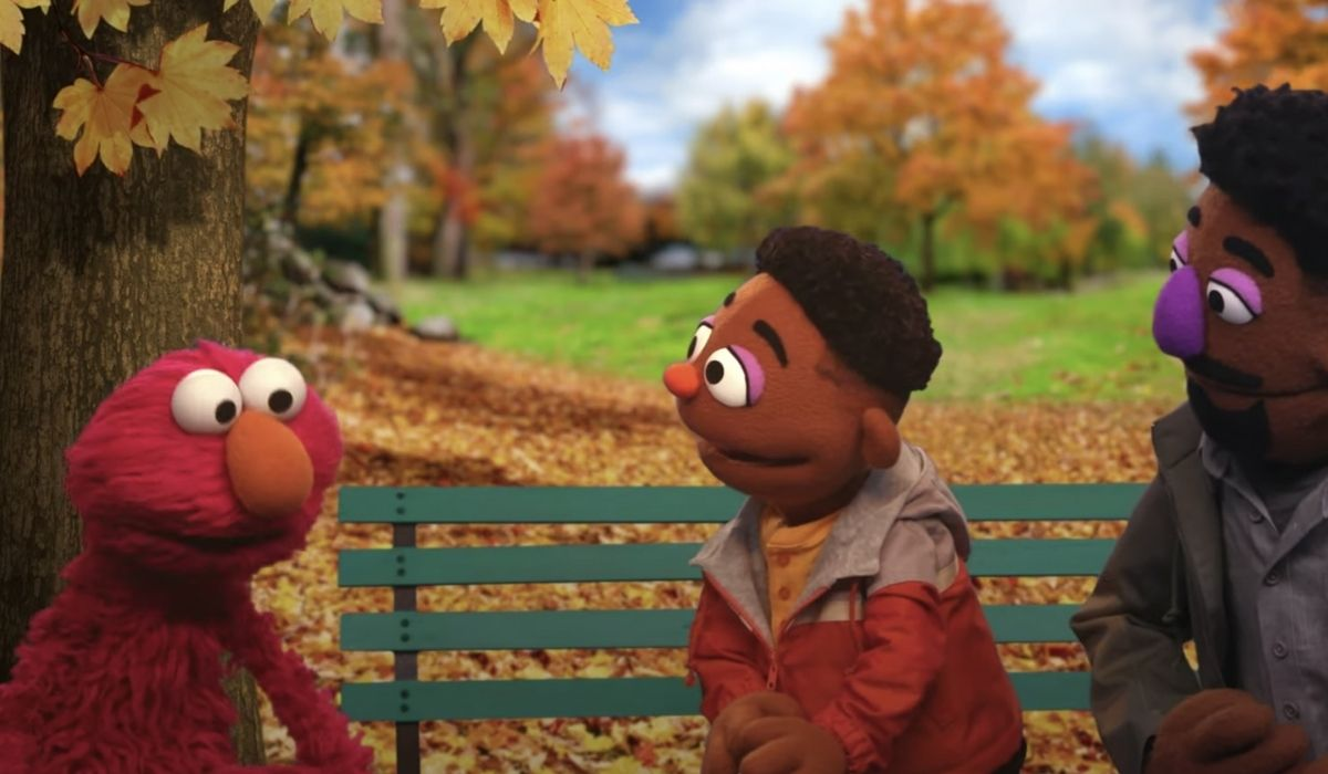 Elmo talking with a Black child and parent at a park. (Image: Sesame Street/HBO.)