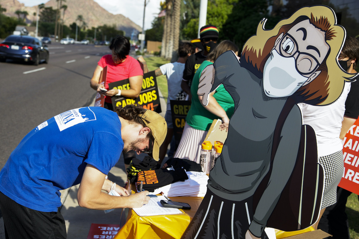 Protesters for green jobs attend a rally featuring a cartoon cutout of Kyrsten Sinema