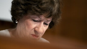 Close up of Susan Collins' face as she looks down