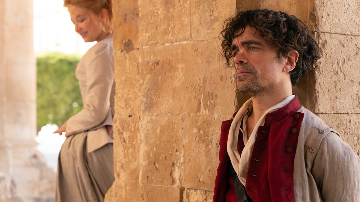 Peter Dinklage and Hayley Bennett standing on opposite sides of the wall in Cyrano